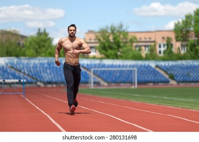 Athlete training. Muscular athlete of the treadmill at the stadium