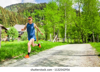 Athlete is training on a country road, Sport and fitness runner man running on training for marathon run. Athlete runner training cardio in nature background.