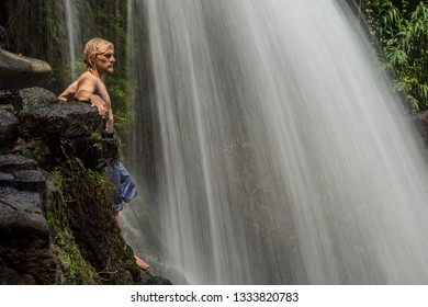 Athlete traveler enjoys of the waterfall with clear water among the jungle of Mauritius