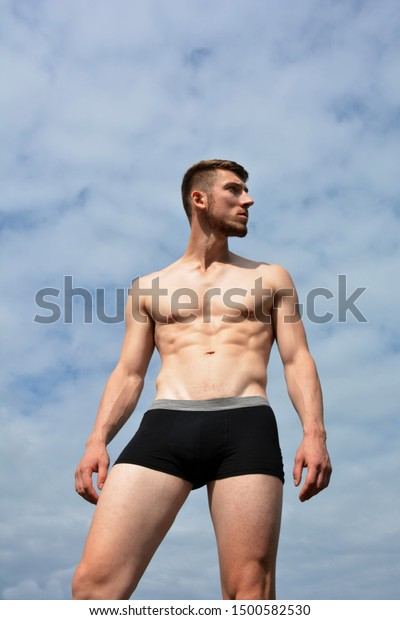Athlete in  underwear on a background of clouds and sun