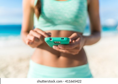 Athlete using mobile phone app fitness tracker for tracking weight loss progress during running exercise. Fit girl woman touching smartphone texting or playing online games or video workouts.