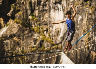 Athlete walking in slackline / highline / tight rope in a rock mountain
