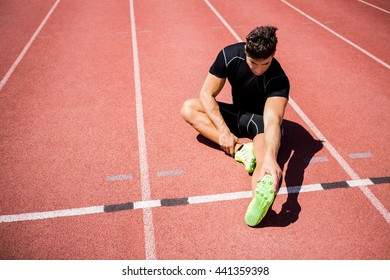Athlete warming up on the running track on a sunny day