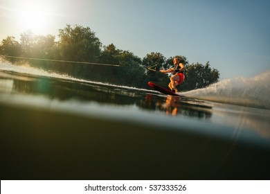 Athlete water skiing behind a boat. Man wakeboarding on a lake.