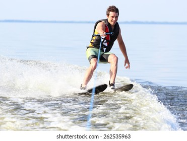 Athlete water skiing and have fun. Summer by the sea.A water skier in his 60's preforming water skiing sport on a lake.