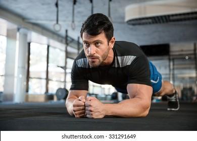 Athlete wearing blue shorts and black t-shirt making static exercise