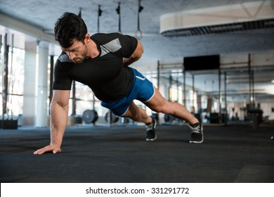 Athlete wearing blue shorts and black t-shirt doing one hand push-ups