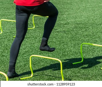 An athlete wearing a red shirt abd black spandex is stepping over yellow mini banana hurdles wearing socks on a green turf field.