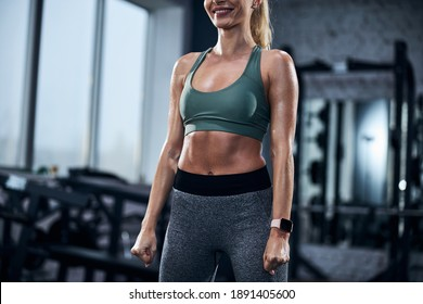 Athlete wearing a sports bra and leggings while staying with her hands put down