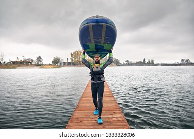 Athlete in wetsuit carries his paddleboard at wooden pier at the lake at cold weather against overcast sky
