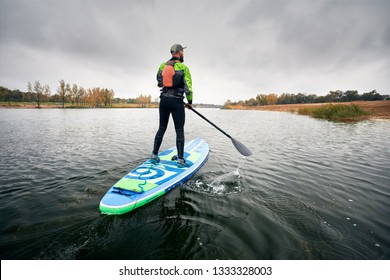 Athlete in wetsuit on paddleboard exploring the lake at cold weather against overcast sky