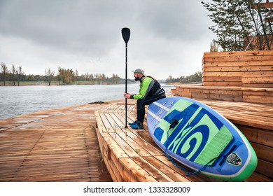 Athlete in wetsuit with paddle and surf sitting at wooden pier near the lake