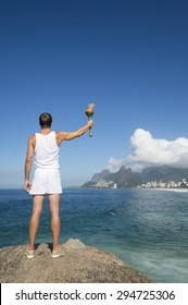 Athlete in white uniform standing with sport torch above Rio de Janeiro Brazil skyline at Ipanema Beach