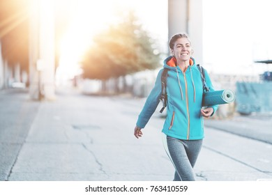 Athlete woman with backpack, headphones, yoga mat going to sport club on the city street. Sport tight clothes. Blurry background.
