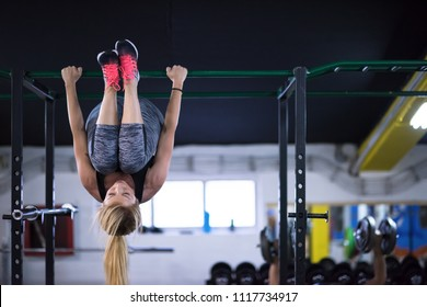 athlete woman doing abs exercises hanging upside down on horizontal bar at cross fitness gym