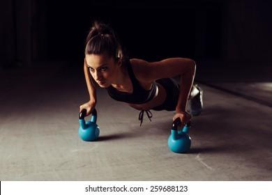 Athlete woman doing push ups on two kettlebells