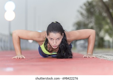 Athlete woman doing push ups and photographed at a very low angle