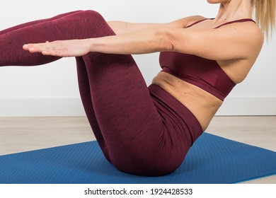 Athlete woman dressed in purple sportswear doing exercises, stretching, pilates and hypopressive exercises with personal trainer. using fitball and fitring