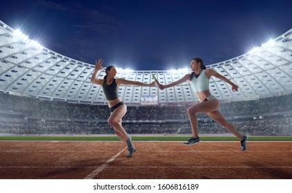 Athlete woman passes the baton at the running track in professional athletics stadium.