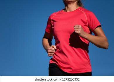 Athlete woman running in red t-shirt and on blue sky background