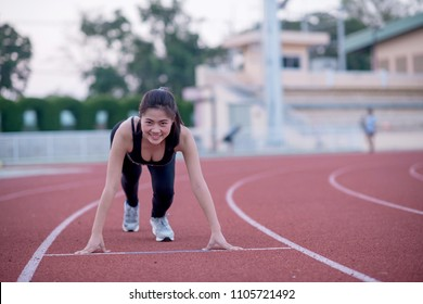 Athlete Woman In Running Start Pose On The Track