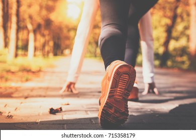 Athlete woman in running start pose on the city autumn park. Sport tight clothes. Bright sunset, blurry background.