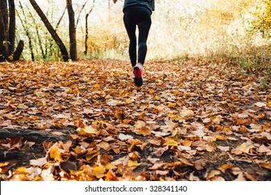 athlete woman runs for fall foliage, shoes closeup