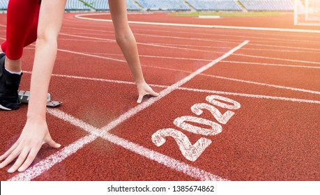 Athlete woman starting on start line with number 2020 ready to run. 2020 year new start concept
