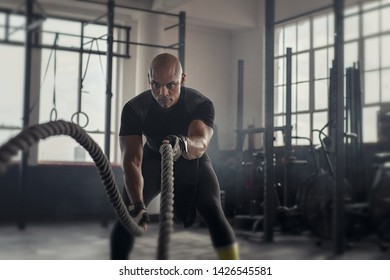 Athlete working out with battle rope at gym. Bald african man training using battle ropes. Fit sportsman doing strength exercise in an industrial dark gym.