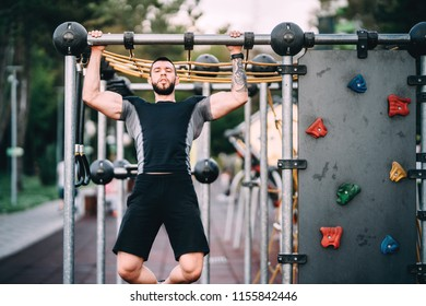 Athlete working out in park, arms and back exercises - pullups