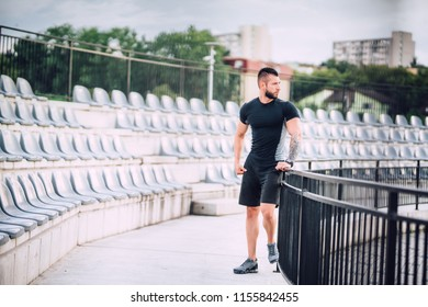 Athlete working out. Portrait of fitness man in park, stadium doing leg workout