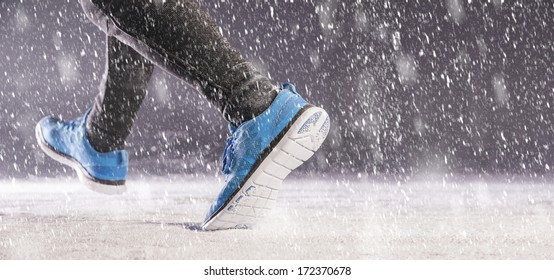 Athleteman is running during winter training outside in cold snow weather.