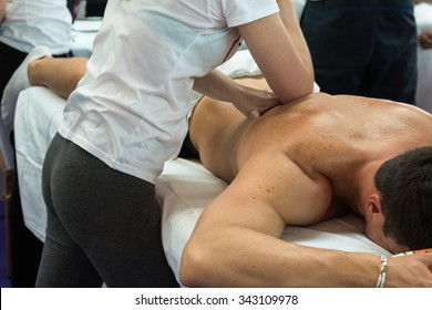Athlete's Back Professional Massage after Fitness Activity by Young Masseuse, Wellness and Sport