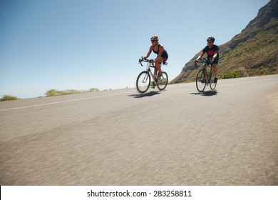 Athletes competing in the cycling leg of triathlon. Triathletes cycling on open country roads. Cyclist riding down hill.
