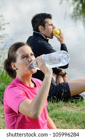 Athletes couple drinking and eating healthy. Sportswoman and sportsman taking a break together after training.