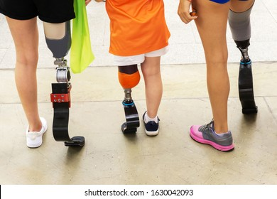 Athletes of different ages with a running leg prosthesis. People with disabilities leading an active lifestyle. The view from the back. Cropped frame.