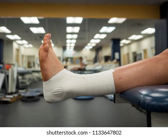 Athlete's foot with an ankle tape job for support hanging off a table in a medical clinic