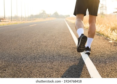 Athletes practice running on paved roads in the soft morning sun.