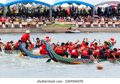 Athletes pulling vigorously on their oars in a competitive boat racing on Keelung River & spectators on the riverbank cheering for their teams in the traditional Dragon Boat Festival in Taipei, Taiwan