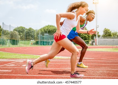 athletes running - mixed race female and male runners training at the stadium on red color running track preparing for sporting event