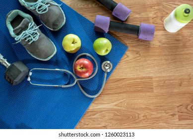 Athlete's set with female clothing, dumbbells , shoesม Heart-measuring device, apple and bottle of water on blue mat ,wooden floor  background - Image