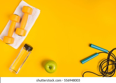 Athlete's set with female clothing, dumbbells and bottle of water on yellow background