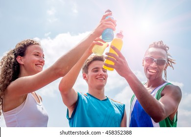 athletes taking a break after training drinking colorful energy drink or sports drink - concept of sports people consuming energetic beverages