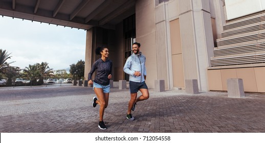 Athletes talking to each other during their morning run. Man and woman in jogging outfit running outdoors in the morning.
