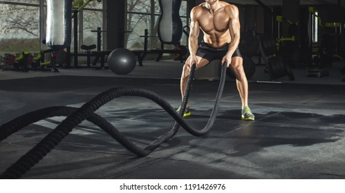 Athletic adult man with battle rope doing exercise in the fitness gym. Sports concept.