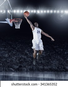 Athletic African American Basketball Player scoring a layup basket during a professional basketball game in a crowded arena