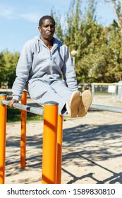 Athletic african  american male performs warm-up exercises at chin-up bar in park