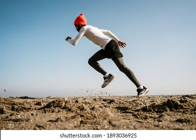 Athletic african american sportsman in earphones running while working out at beach