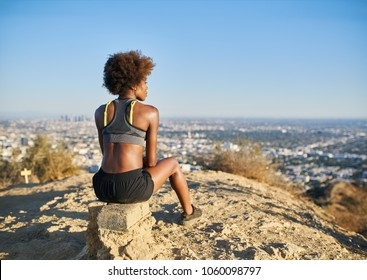 athletic african american woman resting at top of runyon canyon looking at view of los angeles cityscape