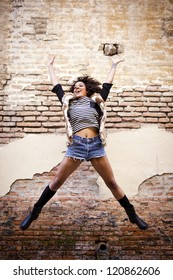 Athletic afro american girl jumping in front of a rusty wall